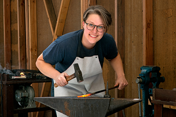 Historic Preservation student Mae Bowley demonstrates blacksmithing technique