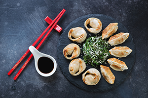 Asian dumplings on plate with chopsticks, soy sauce and green salad.