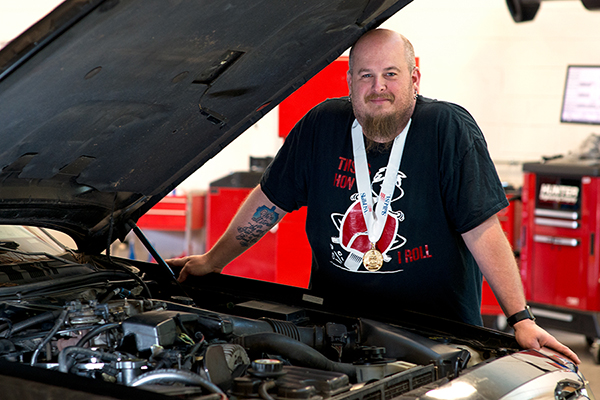 Jonathan Nary wears Skills GA medal and stands by car engine.