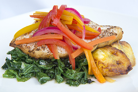 Escovitch fish with peppers over greens