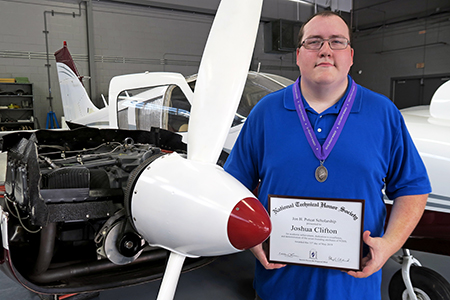 Aviation Maintenance student with certificate near airplane