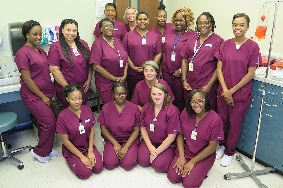 Medical Assisting group of students posing in classroom lab.
